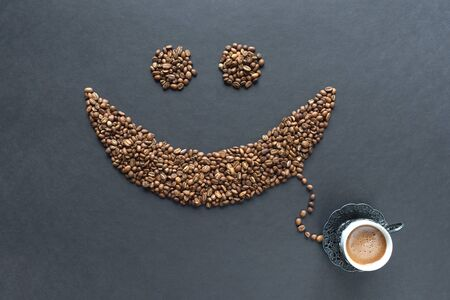 Smiley from coffee beans with cup of coffee on the black background.