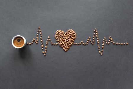 A cardiogram of coffee beans and a cup of coffee on a black background.