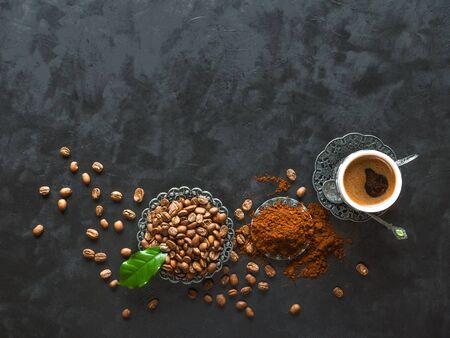 Cup of coffee and coffee beans with ground powder on black background, top view. Imagens