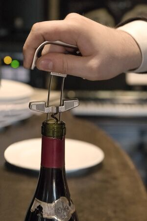 The waiters hand opens a bottle of vintage wine with a corkscrew. Close up. Archivio Fotografico - 129223996