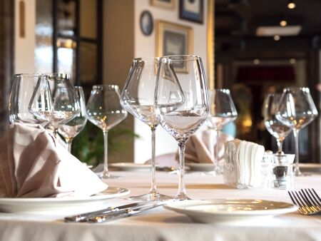 Auf dem Tisch werden leere Weingläser serviert.