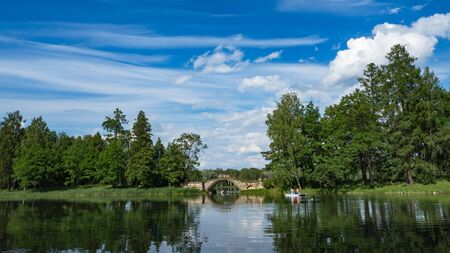 Summer panoramic landscape on the lake with people in boats. Gatchina. Russia. 免版税图像