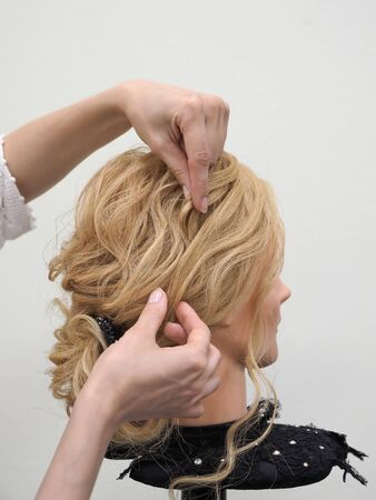 Creation of a fashionable image of a hairstyle on a mannequin.