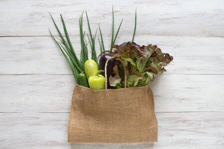 Vegetables in a grocery bag on a wooden table.