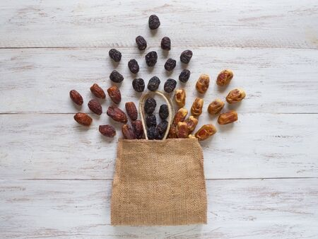 Dates are laid out on a wooden table with a bag.