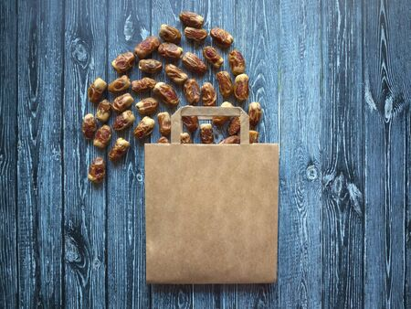 Paper bag with scattered dates on a dark wooden table. Фото со стока