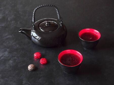 Black teapot of Chinese tea and two cups are on the black table.