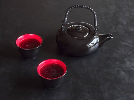 two red cups tea and black teapot on the black table Zdjęcie Seryjne