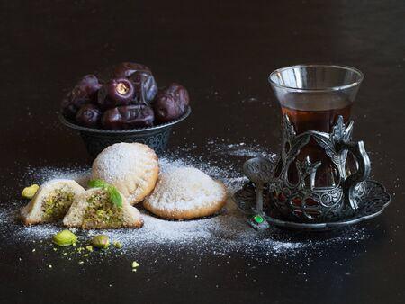 Arabic cookies Maamoul with dates and cup of tea on a black background. Ramadan sweets background Stockfoto