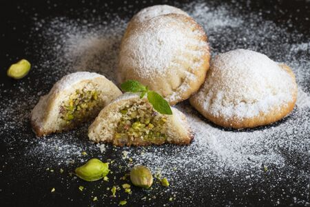 Maamoul - arabic homemade cookies filled with dates and pistachios. Close up.
