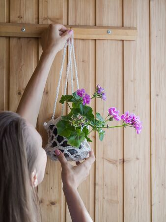 A woman hangs a pot with a potted plant on the wall. Indoor floriculture.