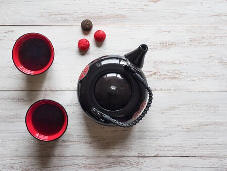 Two red cups tea and black teapot on the white wooden table. Zdjęcie Seryjne