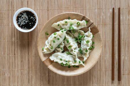 Asian dumplings in bowl, chopsticks, rustic wood background. Chinese dumplings for dinner.