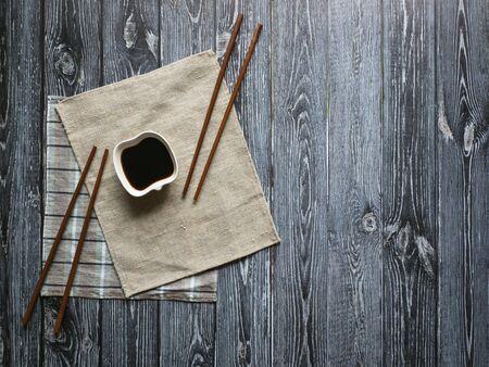 Sauce soja et baguettes sur une table en bois sombre avec espace de copie. Banque d'images
