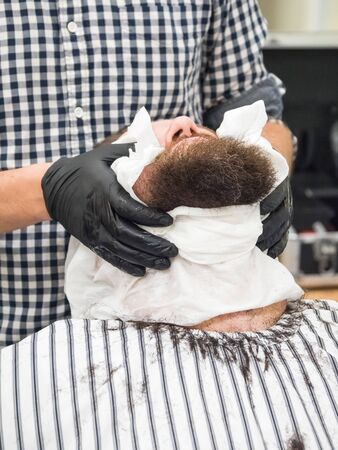 Barber putting warm towel on mans face before giving him shave in Barber shop. Фото со стока