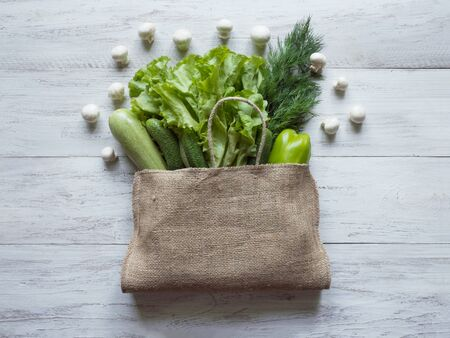 Reusable burlap bag filled with green vegetables, top view on white wooden background.