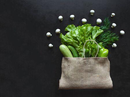 Reusable burlap bag filled with green vegetables, top view on a black background. Reklamní fotografie
