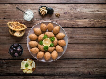 Delicious fried kibbeh with yogurt sauce in a bowl served on a plate on old wooden table. Classic Lebanese recipe.
