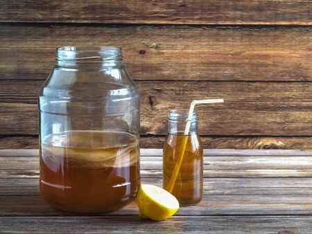 Kombucha by fermenting tea with symbiotic culture of bacteria and yeast on wooden table. Stock Photo