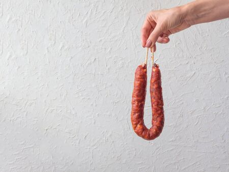 Female hand holds raw meat sausage chorizo on a white background.