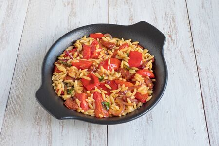 Chorizo orzo salad with roasted pepper, red onion and cherry tomatoes. Top view,