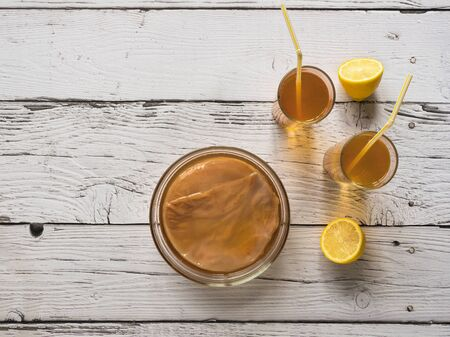 Kombucha fungus. Organic fermented tea drink with lemon on a white wooden table. Stock Photo