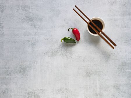Soy sauce with chopsticks and hot pepper on the table. Copy space. Banque d'images