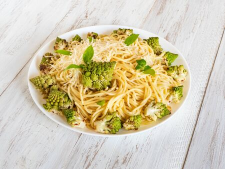 Pasta with romanesco cauliflower (broccoli) on a white wooden table.
