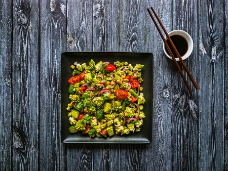 Organic vitamin salad with romanesco cabbage on black table. Asian food.