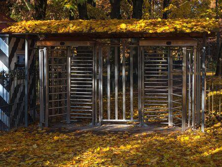 Turnstile, restricted entry. Gates to autumn Park.