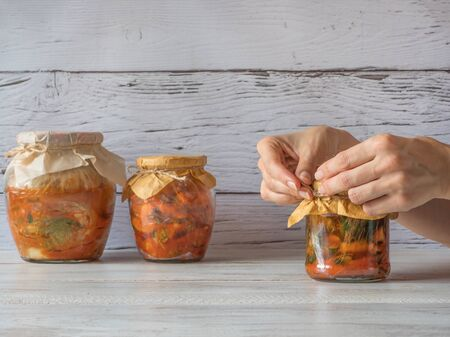 Korean kimchi in jars on a white wooden table.
