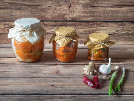 Various kimchi in glass jars on a brown wooden table.