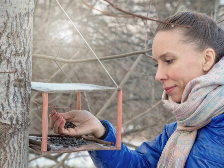 Pretty woman feeds birds on winter park.