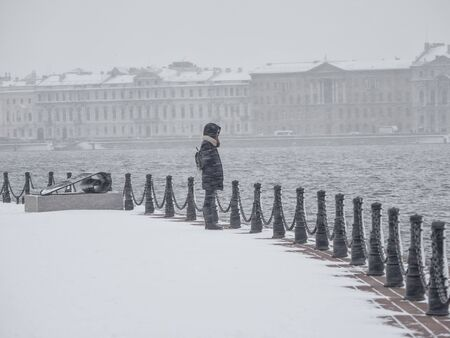 A lonely girl under heavy snow in winter Saint-Petersburg.