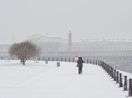 Woman with umbrella under snowfall. St. Petersburg.