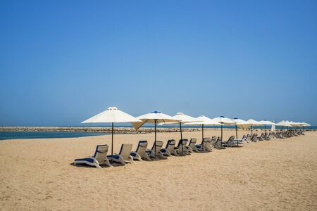Beach umbrellas are in one line. Ras Al Khaima on the Persian Gulf.