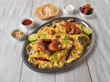 Chicken Mandi with dates on a wooden table. Arabic cuisine. Top view.