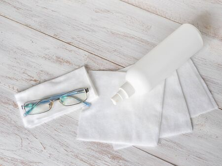 Disinfection of glasses concept. Cleaning protection glasses with alcohol spray and wipe out with cleaned paper.