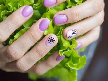 Creative manicure with painted coronavirus on the nails, soft focus, close up. Stock Photo
