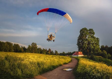 Extreme sports. Powered parachute in the evening against the blue sky.