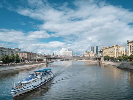 Large two-story white liner with tourists goes along Moscow river. Bridge over river in distance on background of cityscape, blue cloudy sky Banco de Imagens