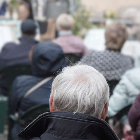 An active pensioner listens to Opera. Back view of the man with a gray hair head in a open air.