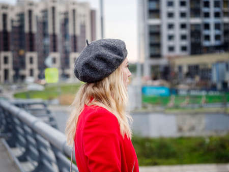 Portrait of a blonde woman in a red coat and beret on a blurry urban background. Foto de archivo
