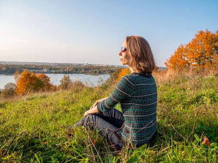 An active, elegant, middle-aged blonde woman in sunglasses is relaxing sitting on a hill with beautiful views in autumn. Standard-Bild