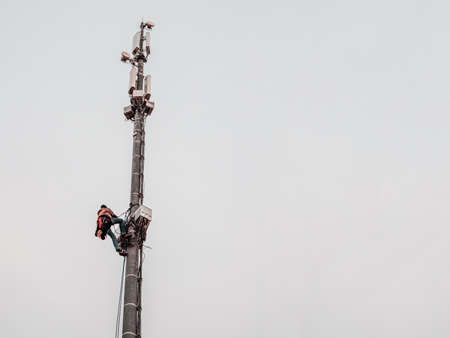 A high-rise worker works on a cell tower. Фото со стока