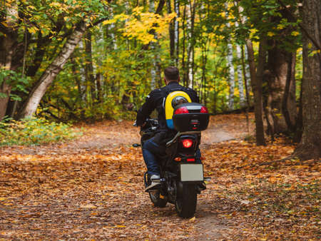 Biker on a motorcycle rides along a forest road with a dog in a backpack on his back Standard-Bild - 157344892