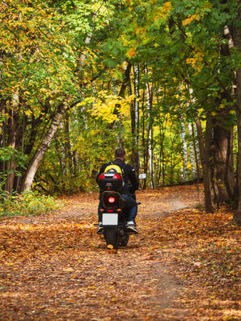 A biker on a motorcycle rides along a forest road with a backpack on his back. Picnic in nature.