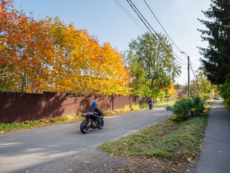 Two bikers on motorcycles ride on a rural autumn road