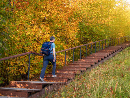 A man with a backpack climbs the eco trail in autumn, bottom-up view Standard-Bild