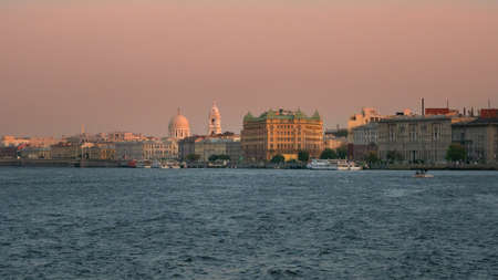 Beautiful pink sunset in Saint Petersburg. Embankment with ancient architecture in the evening.